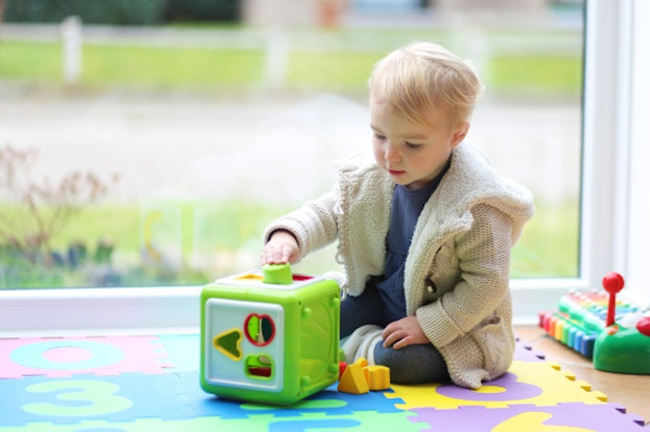 Cute blonde toddler girl playing indoors with sorter toy