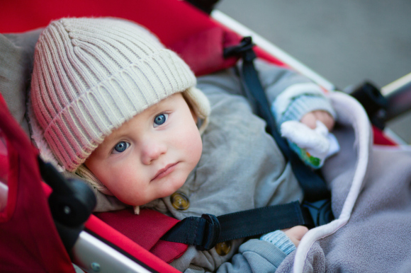 Little boy with blue eyes in a stroller
