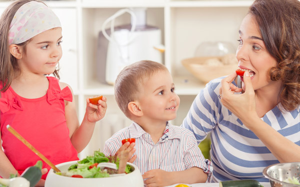 Mother and two children preparing and eating fresh vegetable salad